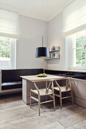 Malý snídaňový stůl je umístěný přímo v kuchyni. Doplňují ho židle z ohýbaného dřeva Wishbone, design Hans Wegener, a svítidlo Twiggy od Foscarini.