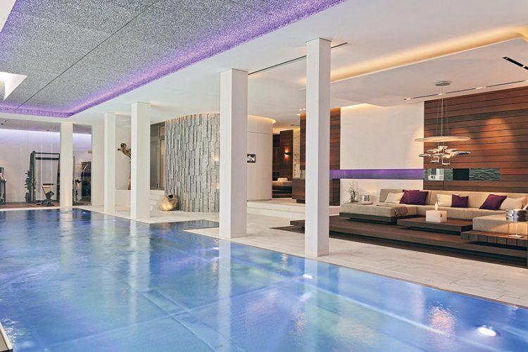 Relaxační prostor v suterénu vily je nadstandardně vybaven. Bazén propojuje fitness s odpočinkovým koutem, umístěným na pódiu z masivního dřeva. Lustr od Artemide podtrhuje luxusní pojetí prostoru.