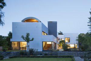 Bělostnou fasádu tvoří panely z novodobého materiálu HI-MACS. Spáry mezi deskami tvoří pravoúhlý rastr, který ladí s tvaroslovím stavby.