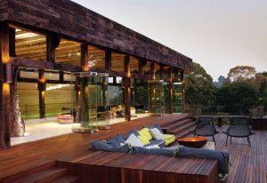Venkovní posezení je zapuštěné ve stupňovité terase. Šedá a citronová barva polštářů tvoří příjemný kontrastní prvek v záplavě hnědočervené barvy exotického dřeva