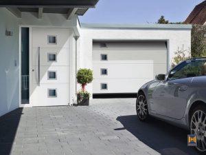 Příklad souladu garážových vrat a vstupních dveří. Vrata LPU 40 s drážkou ve tvaru L, hladkým bílým povrchem Silkgrain a s designovým motivem stojí 22 120 Kč. Cena domovních dveří TopComfort ve stejném designu se pohybuje od 90 850 Kč. Hörmann