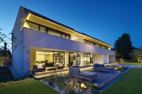 Impozantní vila se prosklenou jižní fasádou, která funguje jako spojnice interiéru s exteriérem, obrací do dokonale upravené zahrady. Zajímavým funkčním a pohledovým prvkem je pás jemného LED osvětlení, chytře začleněného do okapového systému podél okraje střechy.