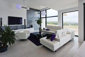 Sedací zóna v obývací části pokoje je o dva stupně snížena oproti hale s jídelnou. Kopíruje tak úroveň terénu a zároveň je v této části domu vyšší strop.
