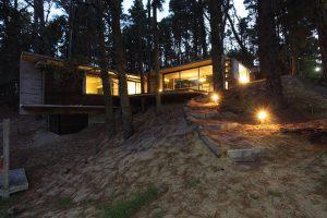 Obrázek zachycuje dům ve večerních hodinách. Světlo z interiéru příjemně prostupuje do lesní krajiny celoprosklenými stěnami. Osvětlena je i přístupová cesta, která je kromě betonových dílců oddělujících nášlapy zcela přírodní.