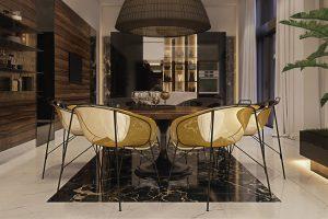Jídelní stůl plynule navazuje na kuchyňský pracovní ostrůvek. Punc luxusu autorka umocnila designovými jídelními židlemi se zlatými sedáky a kovovou konstrukcí. Autorem lustru BELL, umístěného nad stolem, je Manuel Vivian pro Axolight.