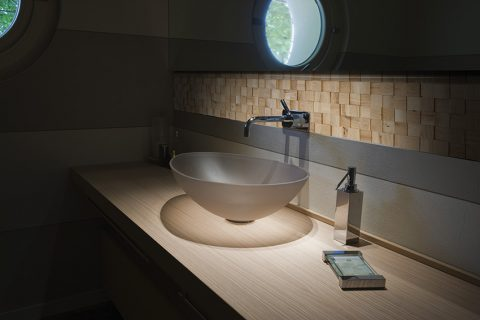 OZDOBOU DESIGNOVÉ KOUPELNY je pruh dřevěné Mosaici d´Asolo na stěně za umyvadlem, dřevina/dekor dub, 3D efekt. V nabídce je také dub perleťový, jemně šedý a středně hnědý, dále dřeviny teak a wenge. Cena od 3 691 Kč/m2. KRATOCHVÍL PARKET PROFI, www.kpp.cz