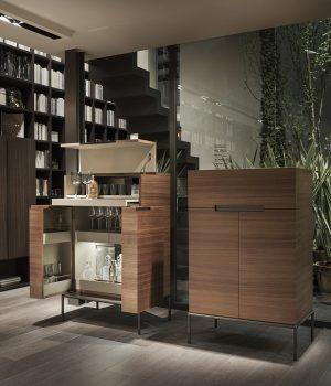 WINSTON, design Christophe Pillet. Barová skříňka v ořechové dýze nabízí výklopné horní víko, výsuvný pultík, vnitřní osvětlení a prostor pro vybavení domácího baru. LEMA, www.lema.it