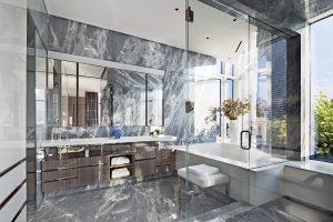 Velká zrcadlová stěna nad deskou se zapuštěnými umyvadly ještě násobí prostor koupelny. Skleněná stěna oddělující šatnu tvoří téměř neviditelnou hranici mezi místnostmi a nechává volně proudit denní světlo.