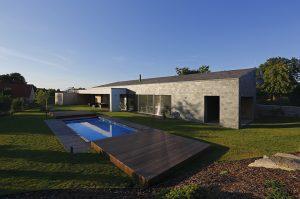 Zahradě dominuje bazén obklopený pochozími plochami s obkladem z dřevěných fošen Thermowood. Fasádu hlavního traktu zdobí obklad z přírodní břidlice, šablony ze stejného materiálu pokrývají i pultovou střechu.