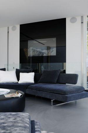 Salon končí u čiré skleněné přepážky ve funkci zábradlí, za ní vede schodiště o podlaží níž – k ložnicím. V panelu z černého skla je na stěnu umístěna velká televizní obrazovka, obrácená k posezení