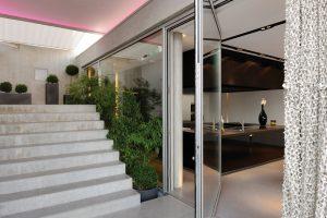 Venkovní, pro změnu bílé, široké schodiště vede od vstupu na prostornou venkovní terasu a skleněnými stěnami dál do interiéru