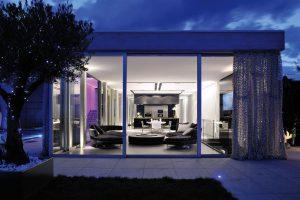 Průhled z terasy do interiéru rozkrývá uspořádání jednotlivých společenských zón – odpočinkový salon přechází v jídelní a kuchyňskou