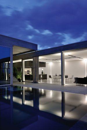 Díky celoskleněným stěnám se večerně osvětlený interiér vily odráží na poklidné hladině venkovního bazénu na terase