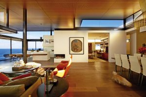 """Horní část dvoupatrového domu s vysokým stropem má charakteristiku """"piano nobile"""", reprezentativních společenských prostor. Kromě na terasu otevřeného obývacího pokoje s jídelnou, kuchyní a pracovnou obsahuje i ubytování pro hosty. Vybavení interiéru dominuje dřevo na podlahách a stropech."""