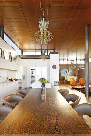 Vnitřní jídelna navazuje přímo na minimalistickou kuchyni v bílé barvě. Na ostrůvek navazuje barový stůl s vrchní deskou ze dřeva s výraznou kresbou, který obklopují stoličky s koženým polstrováním.
