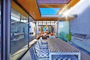 Venkovní kuchyně odstíněná od sousedního pozemku betonovou stěnou je vybavena komfortním grilem a stylově odpovídajícím nábytkem. Zpracování vrchní desky stolu je shodné s materiálem a vzhledem dlouhé lavice.