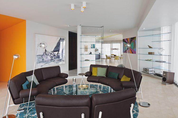 Centrem penthousu je společenská zóna s kruhovým posezením. Na míru zhotovené kožené pohovky lemují kulatý, zakázkově vyrobený koberec, minimalistické vybavení doplňují skleněné police.
