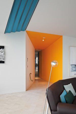 Sytá oranž na části stěn zvýrazňuje trychtýřovitý vstup do multifunkční společenské zóny s obývacím pokojem. V použitém barevném spektru má znázorňovat hřejivý západ slunce.