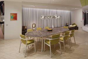 Prostoru jídelny vévodí oválný stůl s vrchní deskou z dekorativního přírodního mramoru. Podlaha je obložena dlažbou z odolného leštěného travertinu.
