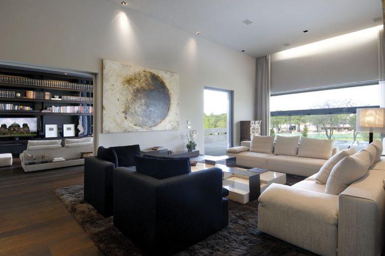 Bílo-šedo-černou barevnou škálu interiéru společenské zóny doplňují syté zemitě hnědé doplňky. Zejména huňatý vlněný koberec dodává vysoké místnosti pocitové zateplení