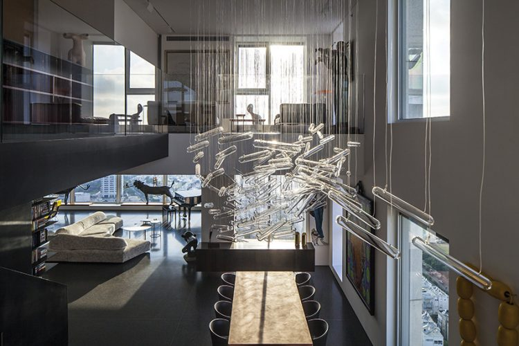 Duplex je zčásti otevřen do druhého obytného podlaží, díky čemuž vznikla působivá horní galerie. Řešení dotahuje k dokonalosti designový lustr, sestavený ze samostatně zavěšených uzavřených skleněných trubic.