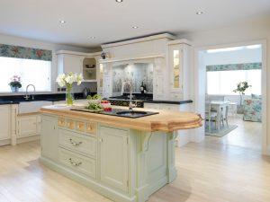 TYPICKÉ DETAILY tradičního anglického designu, jako jsou ozdobné točené pilastry či nápisy na čelech zásuvek, zdobí zakázkovou kuchyni Erlsmere. Nový vzhled přidávají dřevěné žaluzie a žulové vložky, jež dobře ladí s moderními spotřebiči. Cena zobrazené realizace od 500 000 Kč. STEFF NICKOLSON, http://steff-nickolson.com/