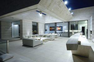 K večerní siestě láká terasa s pohodlným sedacím nábytkem a venkovním barem. Promyšlené osvětlení nejen navozuje příjemnou náladu, ale dává také vyniknout zvolenému architektonickému stylu budovy i transparentním interiérům