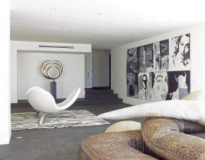 Obytná část působí spíše jako galerie. Černá břidlicová podlaha a bílé stěny tvoří pozadí pro kovovou plastiku Bruna Reymonda a velkoplošný obraz Williama Randa