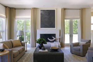 Pohled na prostorný obývací pokoj, který architekt prosvětlil přidáním francouzských oken téměř po celém obvodu. Z obývacího pokoje majitelé přímo vstupují na zahradu a k bazénu. Pokoj je celý otevřený a umožňuje volný průchod do dalších místností v domě. Nad krbem je umístěn obraz od slavného malíře Gerharda Millera