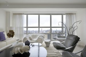 Panoramatické okno v obýváku nabízí výhled na manhattanské mrakodrapy. Pohovku navrhl dekoratér Robert Couturier. Křesílko vpravo pojmenoval jeho autor Paul Tuttle Zeta, zjevně inspirován Miesem van der Rohe. Konferenční stolek v lakovaném bronzu patří do limitované edice designéra Huberta Le Galle. Příjemný dojem umocňuje koberec z bílé vlny alpaky
