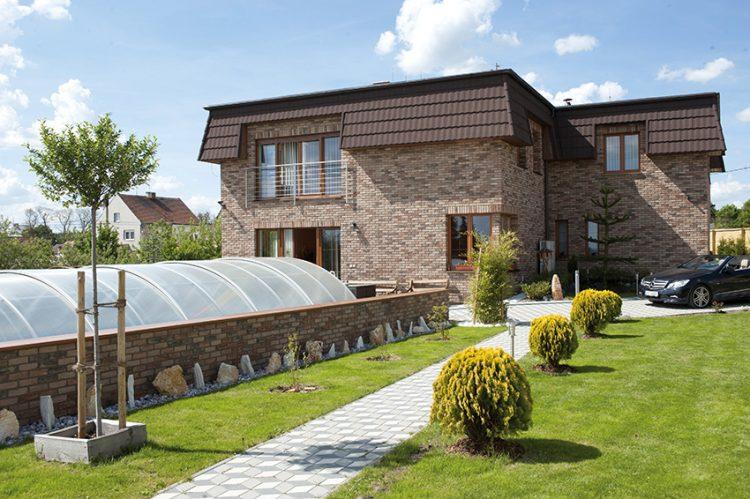 Efektní cihlové pásky Brickland T15 pohledově propojují dům s opěrnou zdí. Cesta vedoucí zahradou a příjezdová komunikace jsou zhotoveny z jednoduché dlažby. Cena cihlových pásků od 641 Kč/m2. BRICKLAND, www.brickland.cz