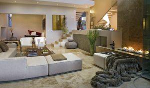 Prostředí obývacího pokoje umístěného uvnitř domu je zútulněné mnoha doplňky. Za pozornost stojí například exkluzivní deka z umělé kožešiny. Materiál k nerozeznání od přírodního originálu potěší všechny ekology