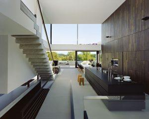 Kuchyňský ostrůvek a stěna obložená tmavým dřevem jsou naladěné v černé barvě. Jako osvěžující prvky působí stoličky z masivního dřeva a detaily z leštěné oceli