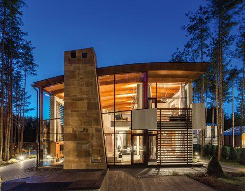 Jemně zakřivené pultová střecha a mohutný komín protínající skleněný obvodový plášť charakterizují luxusní rezidenci obklopenou vzrostlým borovým lesem.